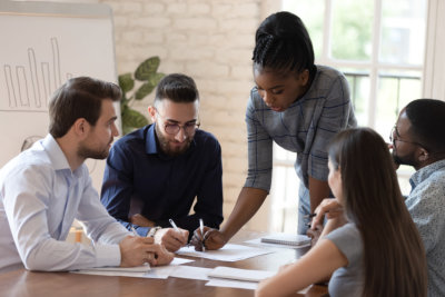 Serious african woman supervisor boss teach diverse staff workers